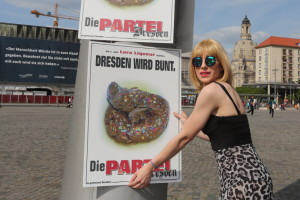 Lars Stosch alias Lara Liqueur (20), Oberbürgermeister-Kandidat von Die Partei plakatiert auf dem Dredner Altmarkt Plakate, die mit Streuseln dekorierte Kackhaufen zeigen. Foto: Christian Suhrbier